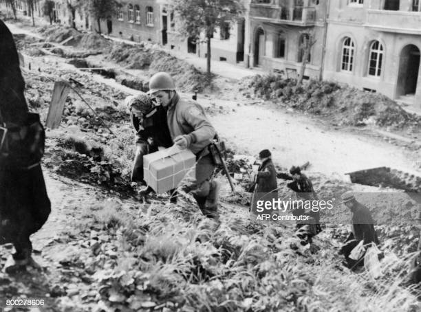 Picture released on October 20 1944 of American soldiers helping civilians to evacuate AixlaChapelle during the Second World War / AFP PHOTO /