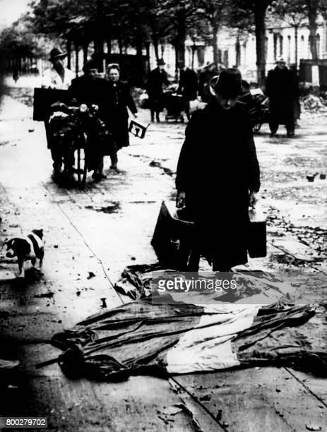 Picture released on October 31 1944 of inhabitants of AixlaChapelle evacuating the German defeated town by walking on the Nazi flag during the Second...