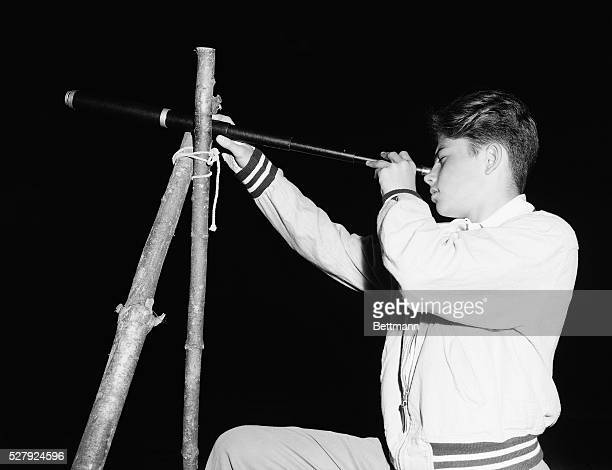 Picture shows a boy looking through the lens of a telescope at night Undated photo circa 1950s