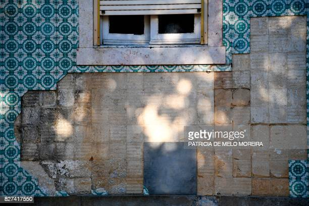 Picture shows a building's facade covered with typical Portuguese titles and showing empty areas due to the missing tiles in Lisbon on July 9 2017...