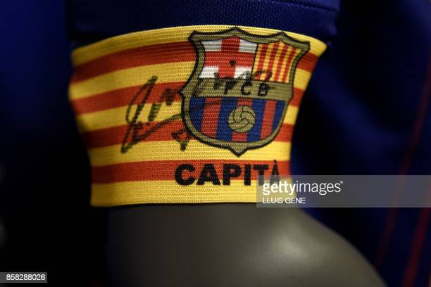 A picture shows a captain armband signed by FC Barcelona's midfielder Andres Iniesta after he renewed his contract at the Camp Nou in Barcelona on...