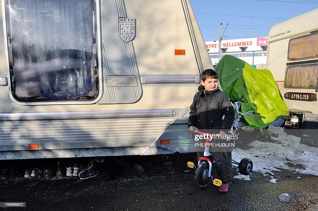 A picture shows a child cycling in a path called 'Chemin Napoleon' covered by snow in a Roma camp on January 22, 2013 in Hellemmes, near Lille, northern France.