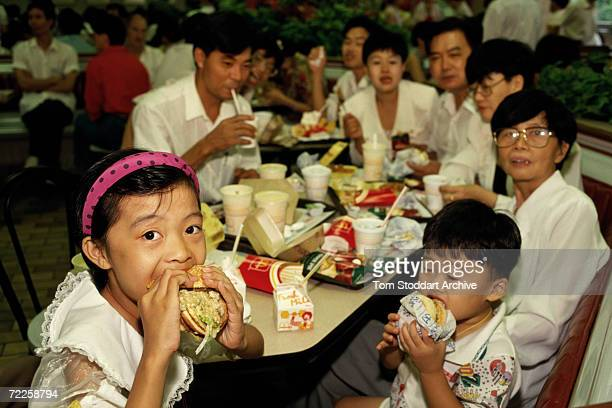Picture shows a family and children enjoying Big Macs inside a McDonalds restaurant in Shenzhen China