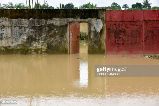 A picture shows a flooded street in a suburb of Abidjan following heavy rainfall in the Ivory Coast on June 13 2017 / AFP PHOTO / ISSOUF SANOGO