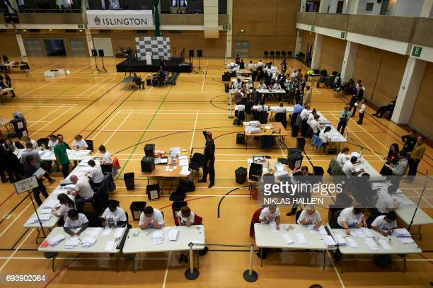 A picture shows a general view as sort counting staff through ballots at a counting centre in Islington London on June 8 after the polls closed in...