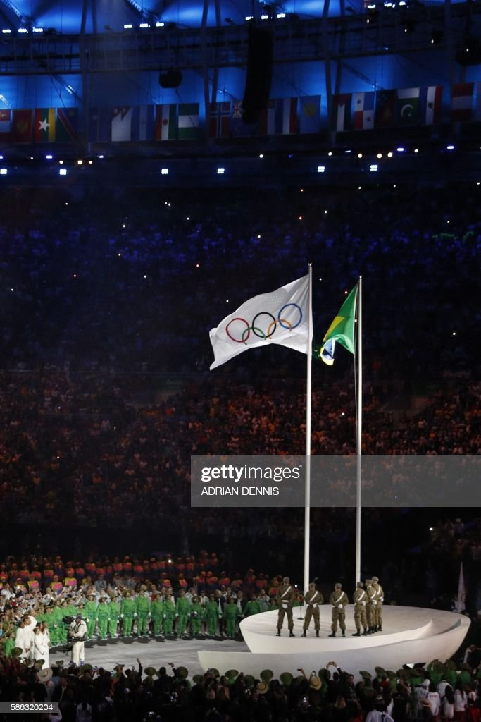 A picture shows a general view with the Brazilian and Olympic flags during the opening ceremony of the Rio 2016 Olympic Games at the Maracana stadium...
