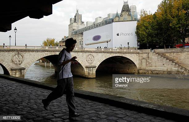 A picture shows a giant iPhone 6 advertising displayed on the facade of the Palais de Justice on October 23 in Paris France This display helps fund...