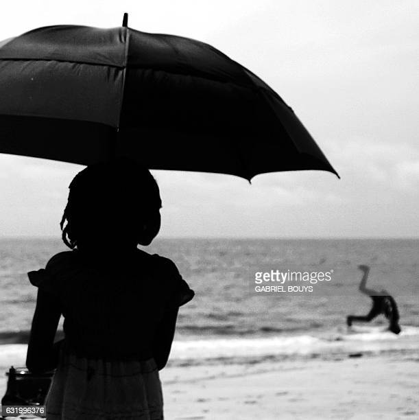 A picture shows a girl holding an umbrella as a man somersaults at a beach in Libreville on the sidelines of the 2017 Africa Cup of Nations football...