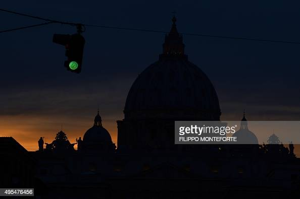 A picture shows a green light next to the silhouette of St Peter's basilica at night on November 3 2015 at the Vatican AFP PHOTO / FILIPPO MONTEFORTE