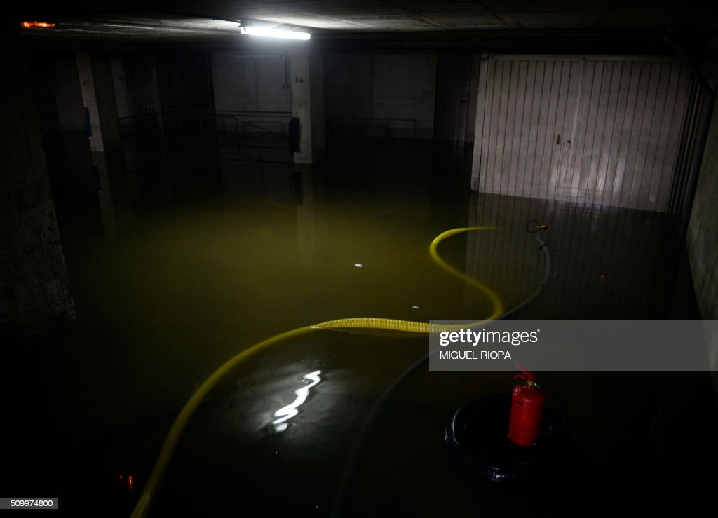 Picture shows a hose floating inside a flooded garage after heavy rains in the village of Redondela, northwestern Spain, on February 13, 2016. / AFP / AFP or licensors / MIGUEL RIOPA