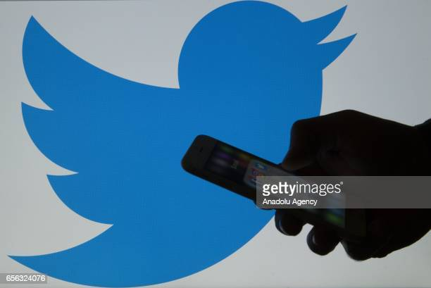 A picture shows a man holding a cellphone in front of a twitter logo in Ankara Turkey on March 16 2017 'Twitter' suspended 636248 accounts for...