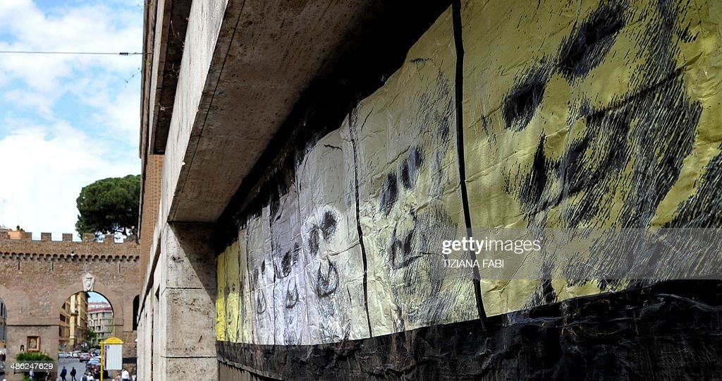 A picture shows a new work of an Italian street artist Maupal, a portrait of the three popes, Pope Francis (C) Pope John Paul II (R) and Pope John XXIII (L), on April 23, 2014 in Rome near the Vatican