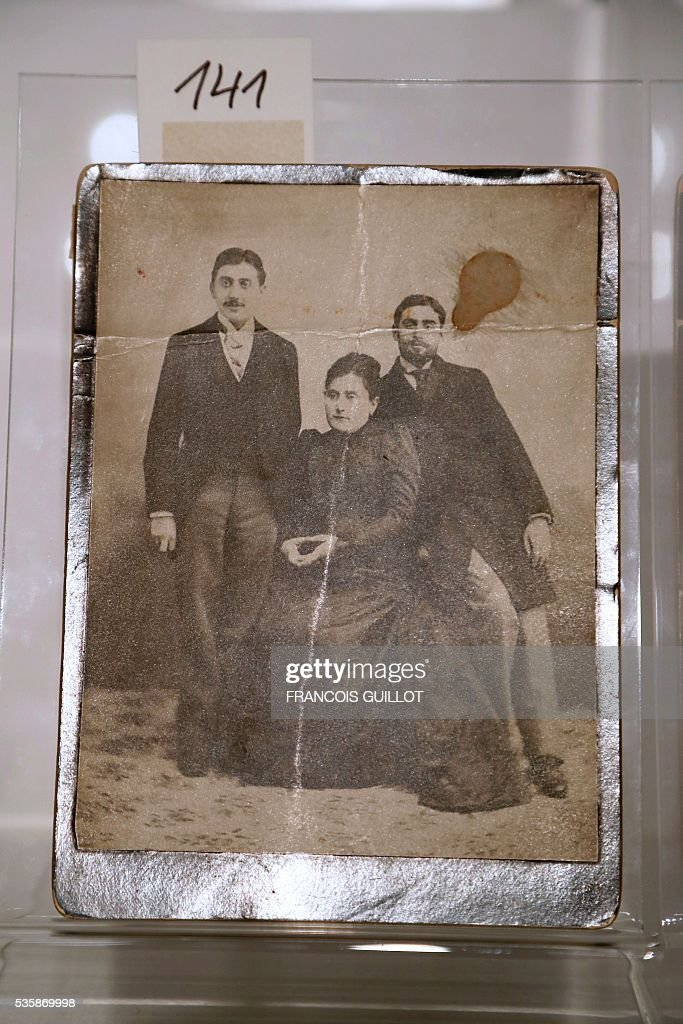 A picture shows a photograph of French writer Marcel Proust (L), his brother Robert (R) and mother Jeanne Weil Proust (C) during the presentation of Proust's personal archives, ahead of an auction at Sotheby's in Paris, on May 30, 2016. / AFP / FRANCOIS