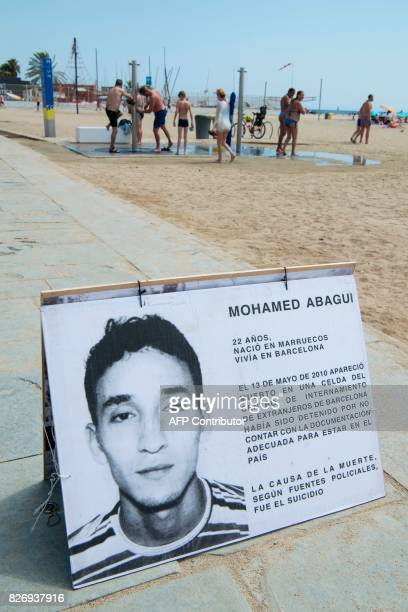 Picture shows a placard telling the story of dead migrant Mohamed Abagui as people use the public showers of Barcelona's Bogatell beach during an...