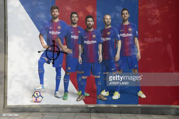 A picture shows a poster of Barcelona FC where the picture of defender Gerard Pique has been vandalised outside the club's Camp Nou stadium which was...