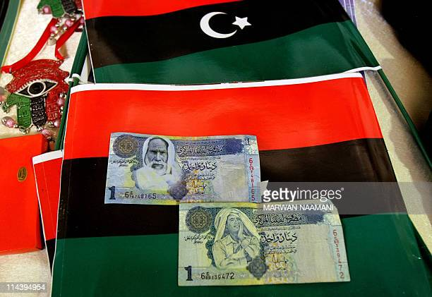 A picture shows a real Libyan dinar bearing the image of Libyan leader Moamer Kadhafi and a fake dinar made by rebels which bears the image of late...