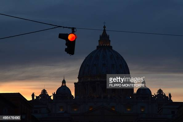 A picture shows a red light next to the silhouette of St Peter's basilica at night on November 3 2015 at the Vatican AFP PHOTO / FILIPPO MONTEFORTE