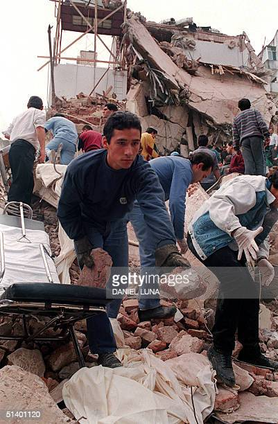 picture shows a rescue worker as he remove the rubbles after the powerful explosion that destroyed a seven storey building housing the Jewish Mutual...