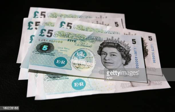A picture shows a sample five pound British polymer banknote sitting on top of normal circulation cotton paper five pound notes during a news...