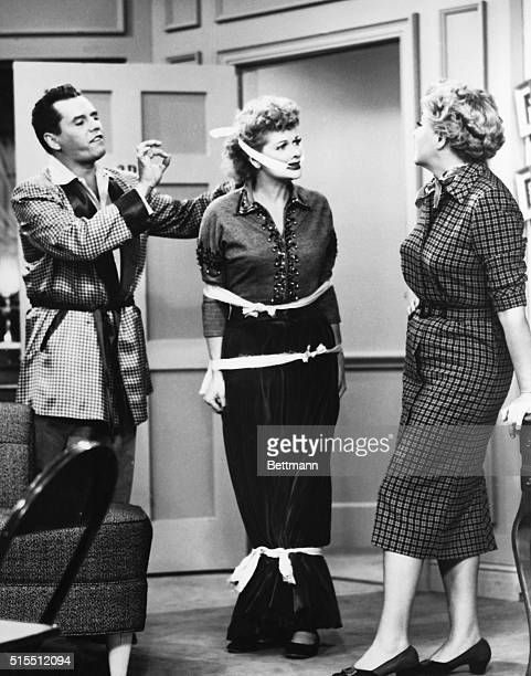 Picture shows a scene from the TV series 'I Love Lucy' Lucille Ball is shown tied up while Desi Arnaz and Vivian Vance stand and watch Undated photo...