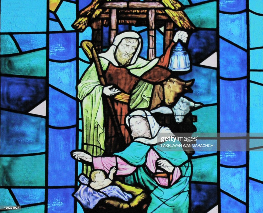 A picture shows a stained glass window depicting the nativity scene during mass in the early hours of Christmas day on December 25, 2013 in Colombo .