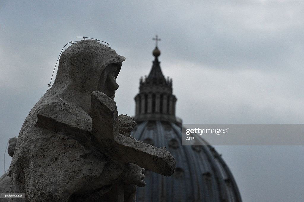 A picture shows a statue of the colonnade and the dome of the St Peter's basilica during the conclave on March 12, 2013 at the Vatican. Cardinals moved into the Vatican today as the suspense mounted ahead of a secret papal election with no clear frontrunner to steer the Catholic world through troubled waters after Benedict XVI's historic resignation.The 115 cardinal electors who pick the next leader of 1.2 billion Catholics in a conclave in the Sistine Chapel will live inside the Vatican walls completely cut off from the outside world until they have made their choice.