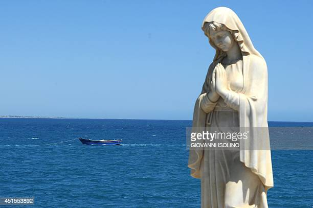 A picture shows a statue of the Virgin Mary and a boat with 30 bodies of immigrants in the background tow by Italian coast guards on July 1st 2014 in...