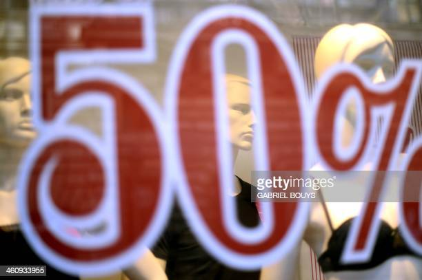 A picture shows a sticker 50 % discount on a shop window during winter sales on January 6 2014 in Rome AFP PHOTO / GABRIEL BOUYS