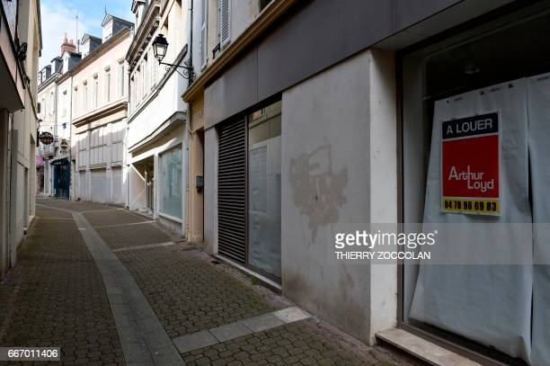A picture shows a 'to rent' sign for a business in Nevers central France on April 4 2017 The population of the picturesque town on the Loire river...
