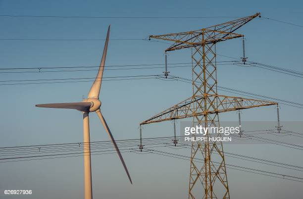 A picture shows a wind turbine near an electricity pylon in Fruges northern France on November 28 2016 / AFP PHOTO / PHILIPPE HUGUEN