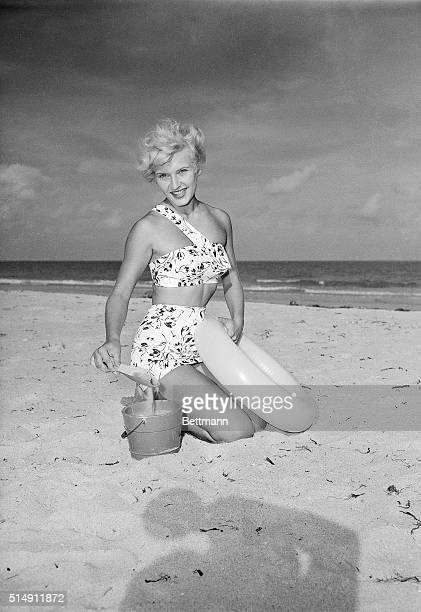 Picture shows a woman modeling a two piece bathing suit on the beach She is shown holding a shovel with a bucket and holding a rubber tube She is...