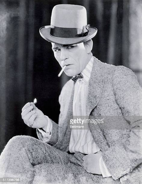 Picture shows actor Lon Chaney Sr posing while lighting a cigarette He is seated and wearing a wool suit and hat Undated photo circa 1910s