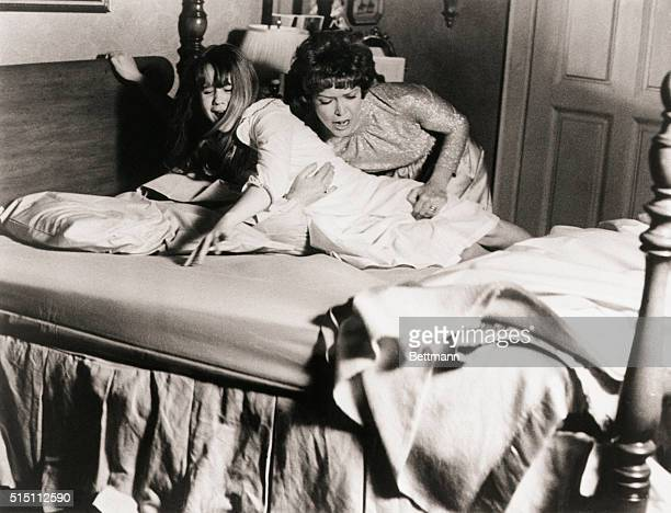 1973 Picture shows actress Ellen Burstyn struggling to keep her daughter actress Linda Blair in her bed during a scene from the 1973 movie 'The...