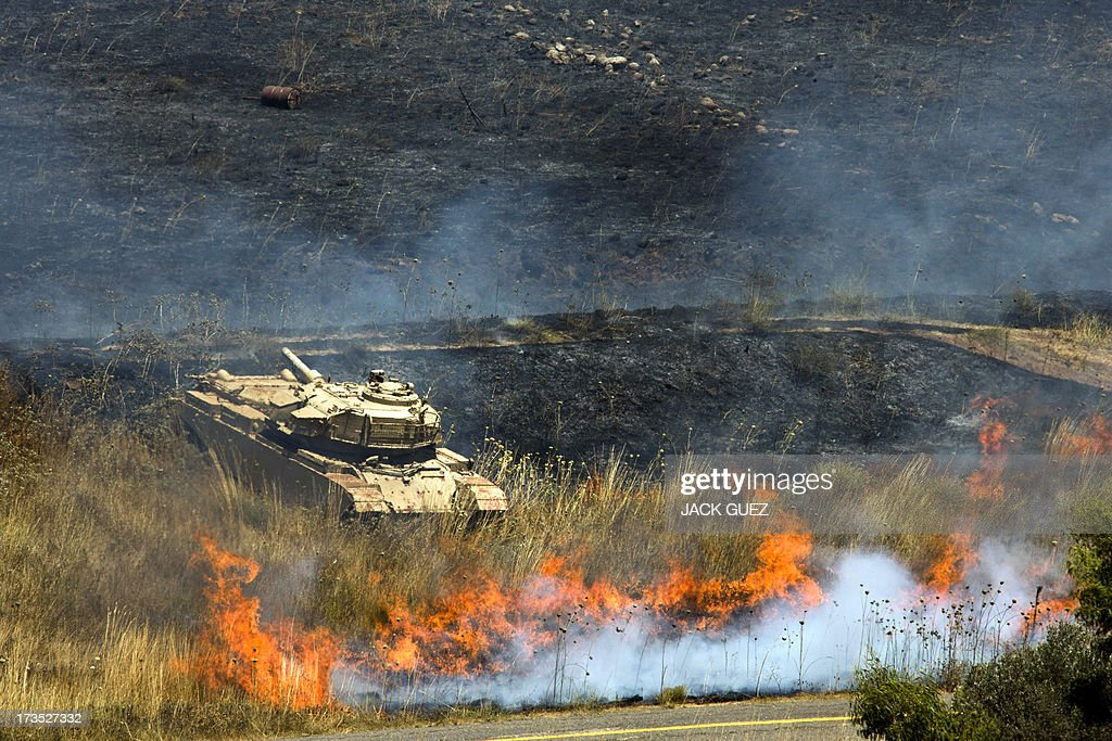 A picture shows an Israeli out of commission army tank near flames after mortar fire from inside war-torn Syria hit the Israeli-occupied Golan Heights on July 16, 2013 causing several wildfires to break out along the ceasefire line. The apparently stray rounds struck as Syrian rebels and regime forces battled near Quneitra which lies in no-man's land, the correspondent reported. Israel, which remains technically at war with Syria, seized 1,200 square kilometres (460 square miles) of the strategic plateau during the 1967 Six-Day War, which it later annexed in a move never recognised by the international community.