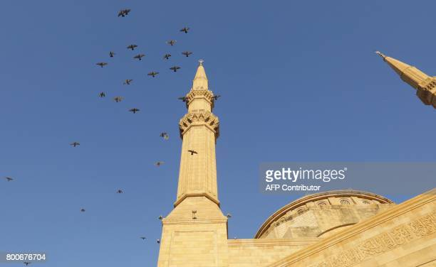 A picture shows birds flying above the Mohammad alAmin mosque in downtown Beirut as people gather to mark Eid alFitr the end of the Muslim holy month...