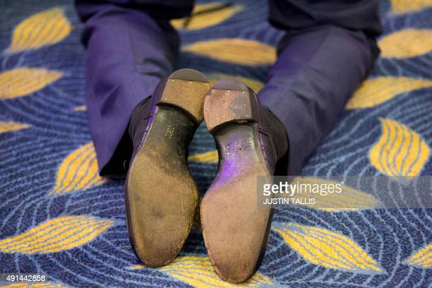 A picture shows brass shoe tacks forming the letter 'H' on the soles of Britain's Prince Harry's shoes as he kneels to speak with award winners...
