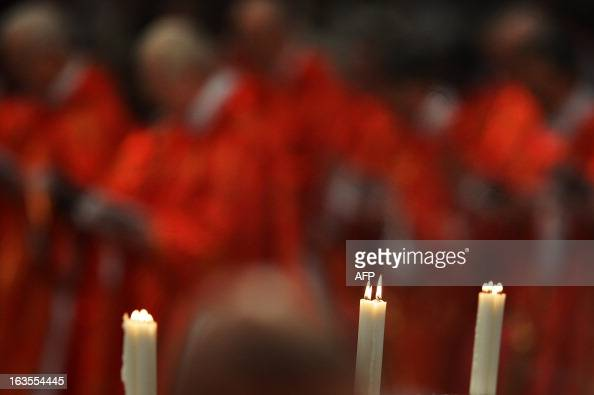 A picture shows candles during a mass at the St Peter's basilica before the conclave on March 12 2013 at the Vatican Cardinals moved into the Vatican...