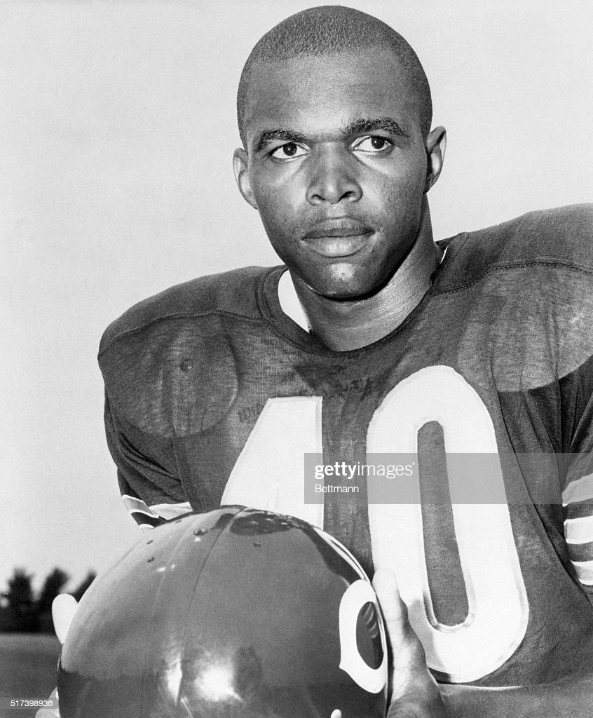 Picture shows Chicago Bears pro-football halfback, Gale Sayers, posing in his uniform holding his helmet. Undated photo.