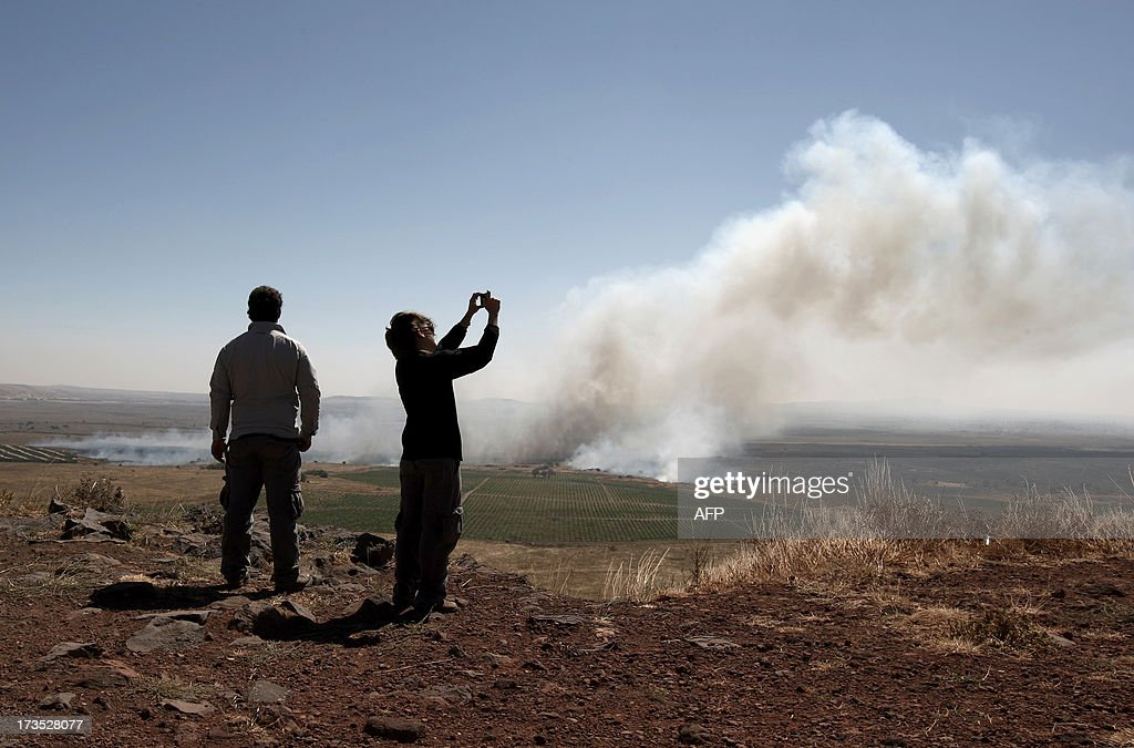 A picture shows civilians taking photographs as smoke billows after mortar fire from inside war-torn Syria hit the Israeli-occupied Golan Heights on July 16, 2013 causing several wildfires to break out along the ceasefire line. The apparently stray rounds struck as Syrian rebels and regime forces battled near Quneitra which lies in no-man's land, the correspondent reported. Israel, which remains technically at war with Syria, seized 1,200 square kilometres (460 square miles) of the strategic plateau during the 1967 Six-Day War, which it later annexed in a move never recognised by the international community. AFP PHOTO / JALAA MAREY
