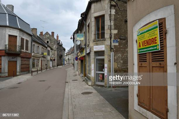 A picture shows closed businesses in Varzy central France on April 4 2017 With its deserted streets 'For Sale' signs and weeds pushing through the...