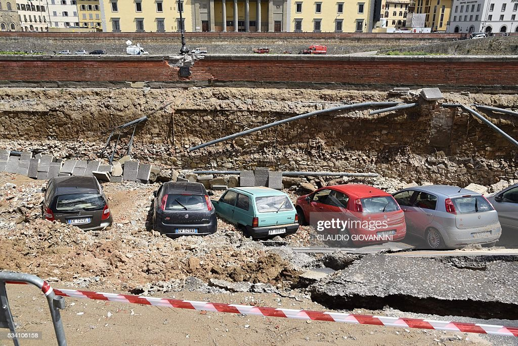 A picture shows damaged cars along the Arno river where the embankment collapsed early on May 25, 2016 in central Florence. The damage, stretching between the 14th century Ponte Vecchio and the Ponte alle Grazie, affected about 200 metres of the embankment in total. Emergency services said the collapse was due to a water pipe break and authorities stopped traffic along the road. / AFP / CLAUDIO