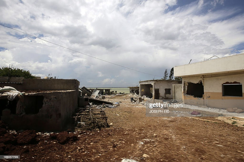 A picture shows damaged houses on the road leading to the village of Ghassaniyeh in the countryside of the rebel city of Qusayr on May 11, 2013. The area has been a strategic boon to Syrian rebels, who used it as a base from which to block the main road from Damascus to the coast, impeding military movement and supply chains. The regime has made recapturing Qusayr a key objective.