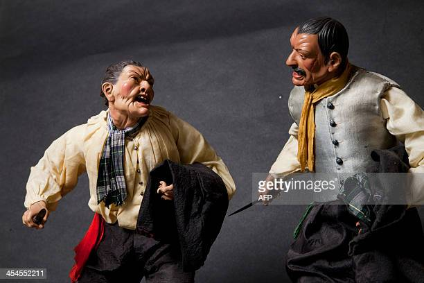A picture shows figurines representing mobsters fighting with knives at the Scuotto's brothers workshop 'La Scarabattola' which sells crib figurines...