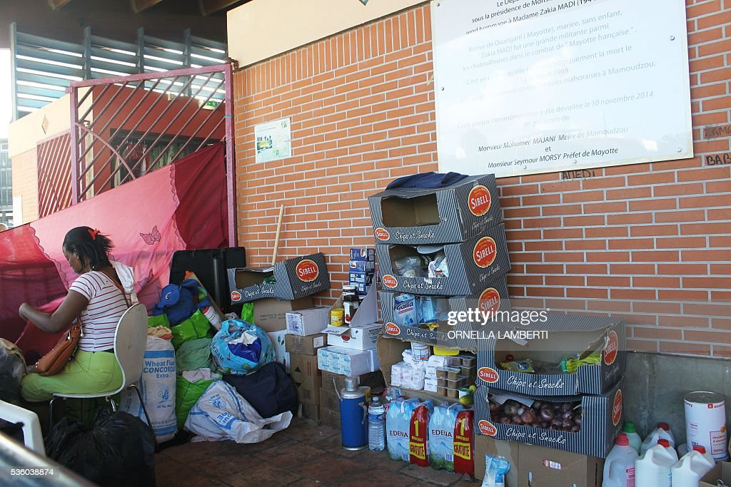 A picture shows food supplies at a makeshift camp on the Place de la Republique in Mamoudzou, on French Indian Ocean territory of Mayotte, on May 31, 2016, where foreigners living in Mayotte have been living after they were expelled from their homes. The police chief of Mayotte said on May 30 that he planned to crack down on clandestine immigration on the French Indian Ocean territory, where locals have forced hundreds of settlers out of their homes. Residents' associations on May 29 issued 'invitations to leave' to migrants in nine Mayotte villages, the prefect's office reported during a crisis meeting on the issue. About 1,000 migrants, almost all from the Comoro Islands in the same archipelago off the coast of southeast Africa, have been expelled from their Mayotte homes by anti-migrant groups since January, according to the local office of rights body La Cimade. LAMBERTI