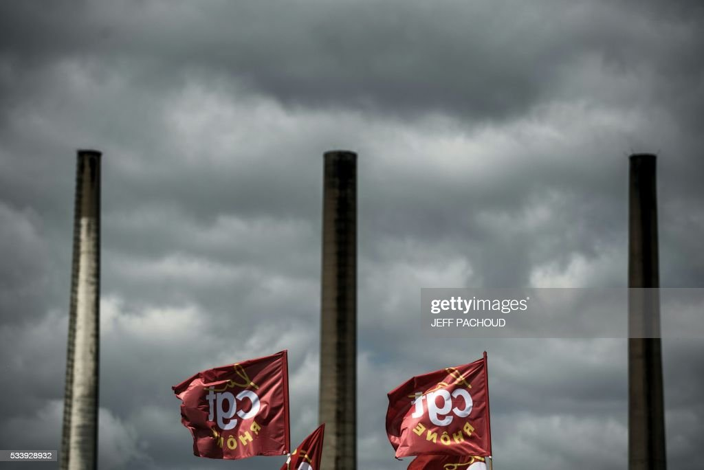 A picture shows French CGT union flags in front of the Total oil refinery of Feyzin, near Lyon, central-eastern France, on May 24, 2016, during a strike at the plant to protest against government labour reforms. France's government stepped up efforts on May 24 to break blockades and strikes at refineries that are threatening to paralyse the country just three weeks ahead of the Euro 2016 football tournament. Six out of eight of the refineries in France have either stopped operating or have reduced output due to strikes and blockades. PACHOUD