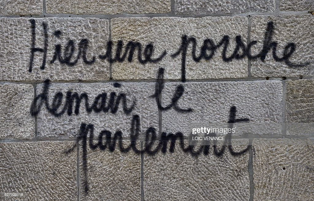 A picture shows graffiti reading 'Yesterday a Porsche, tomorrow the parliament', in reference to a Porsche that was burnt last week during clashes, during a protest against the government's planned labour law reforms in Nantes, western France, on May 3, 2016. High school pupils and workers protested against deeply unpopular labour reforms that have divided the Socialist government and raised hackles in a country accustomed to iron-clad job security. / AFP / LOIC