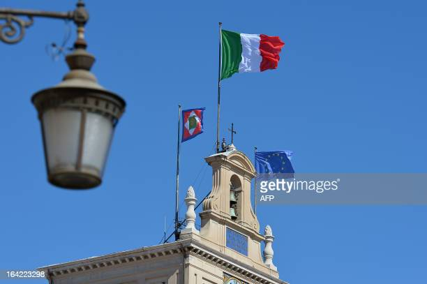 A picture shows Italian flag and the European Union flage on the roof of the Quirinale palace during consulations with political leaders on March 21...