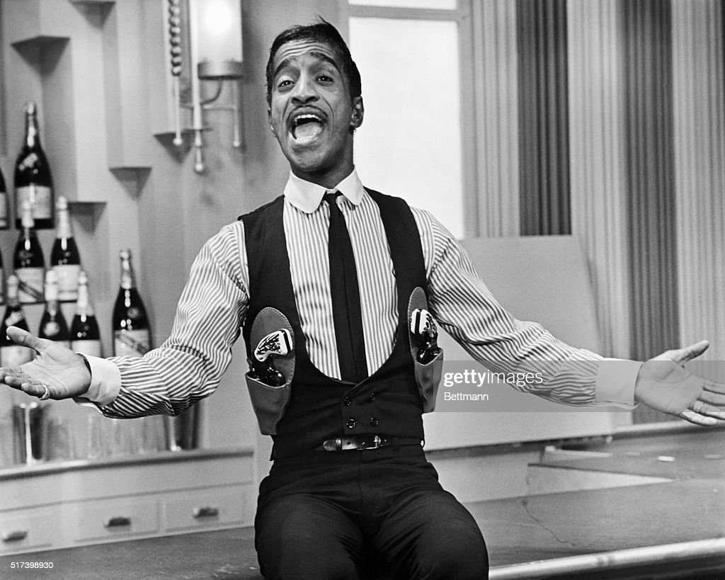 Picture shows legendary performer, Sammy Davis Jr., singing in a gun-slinger's outfit seated on a bar with his arms extended out. Undated photo circa 1950s.