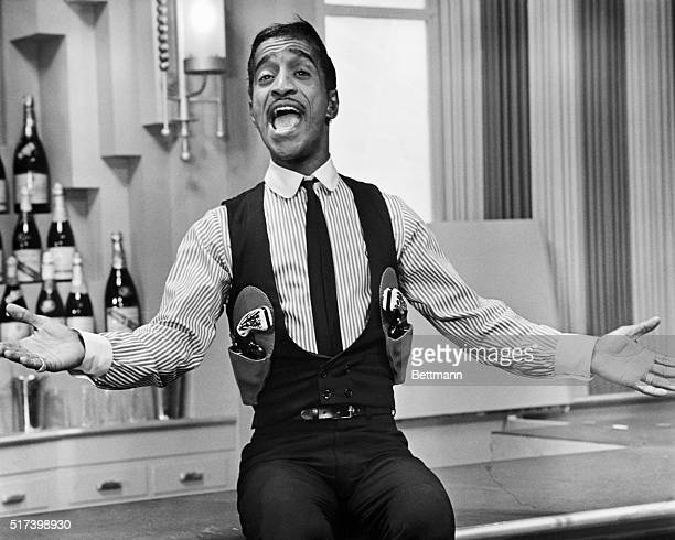 Picture shows legendary performer Sammy Davis Jr singing in a gunslinger's outfit seated on a bar with his arms extended out Undated photo circa 1950s