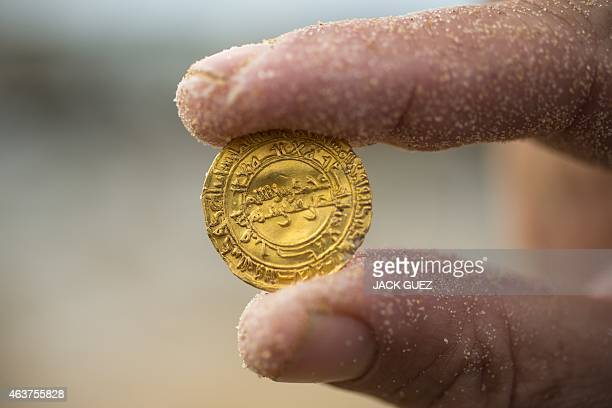 A picture shows one of the gold coins recently found on the seabed off Israel's Mediterranean coast in the Israeli town of Caesarea on February 18...